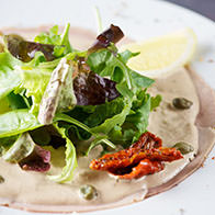 Veal slices with tuna sauce, salad and capers